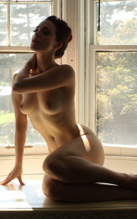 голая блондинка скучает у окна