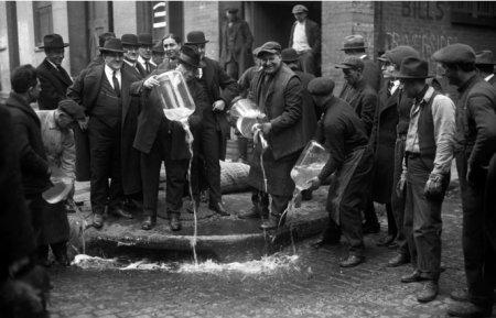 Нью-йоркский ревнитель закона Иззи Энштейн сливает ликер в сточную канаву. 1920 год