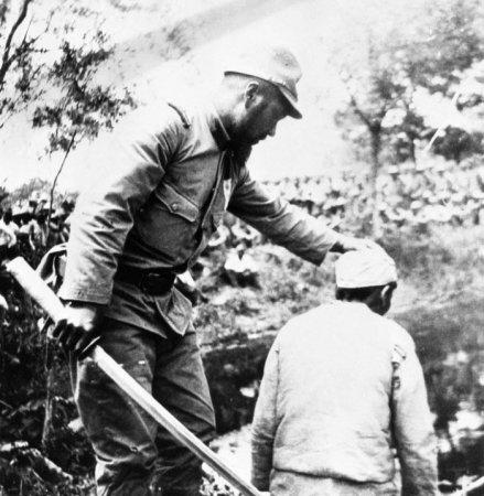 Японский солдат поправляет голову китайцу перед тем, как отрубить её. 1938 год.