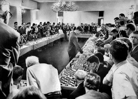 Американский гроссмейстер Бобби Фишер играет одновременно на 50 досках 12 апреля 1964 года. В результате только 1 поражение и 2 ничьих.