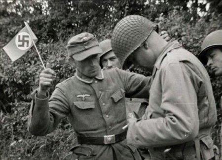 Немецкий солдат с флажком почетно капитулирует перед тремя солдатами союзников.