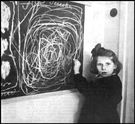 Девочка, которая пережила несколько лет в концентрационном лагере, рисует на доске мелом дом. Польша, 1948.
