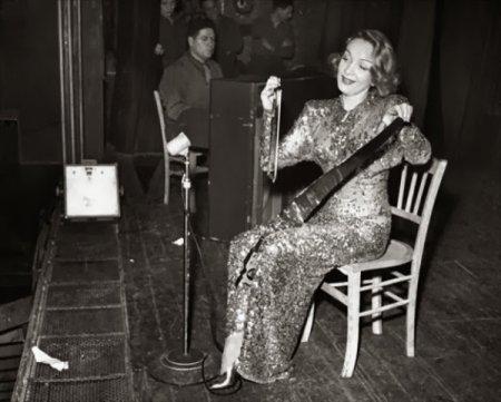Актриса Марлен Дитрих играет на музыкальной пиле. Этот инструмент умер после Второй мировой войны, а актриса была одной из немногих, кто умел на ней играть.