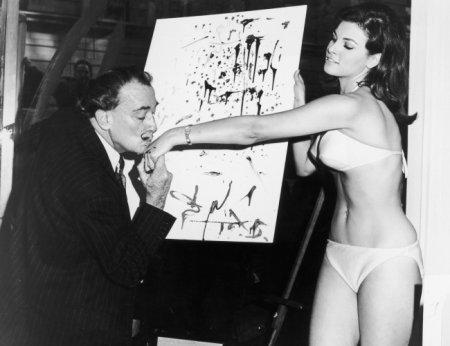 Сальвадор Дали целует руку актрисе Ракель Уэлч на фоне ее абстрактного портрета, 1965