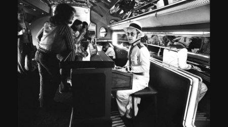 Элтон Джон в пиано-баре на борту своего частного самолета, 1976.